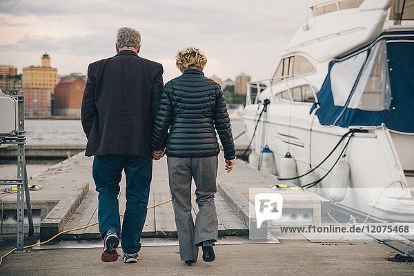 Durchgehende Rückansicht des älteren Paares  das beim Gehen auf dem Pier am Hafen Händchen hält