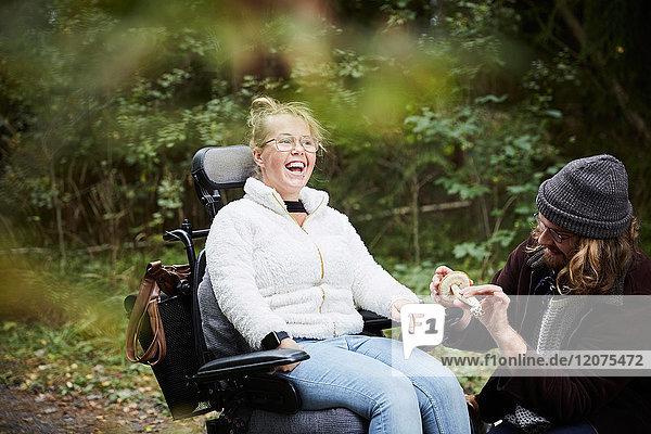Fröhliche behinderte Frau im Rollstuhl von Hausmeisterin mit Pilz im Wald