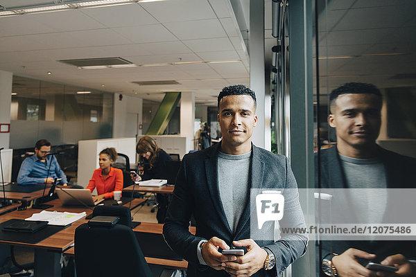 Porträt eines selbstbewussten mittelständischen Geschäftsmannes  der ein Smartphone am Fenster im Büro hält.