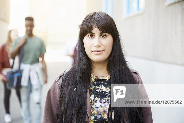 Portrait of young woman with long hair standing at university campus with friends in background