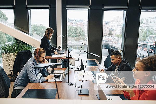 Seitenansicht der multiethnischen Geschäftskollegen am Schreibtisch im Büro