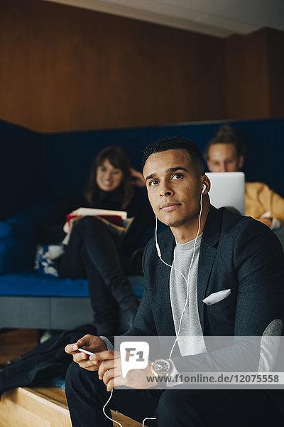 Mittlerer erwachsener Geschäftsmann schaut weg  während er In-Ear-Kopfhörer hört  die gegen Kollegen in der Bürocafeteria sitzen.