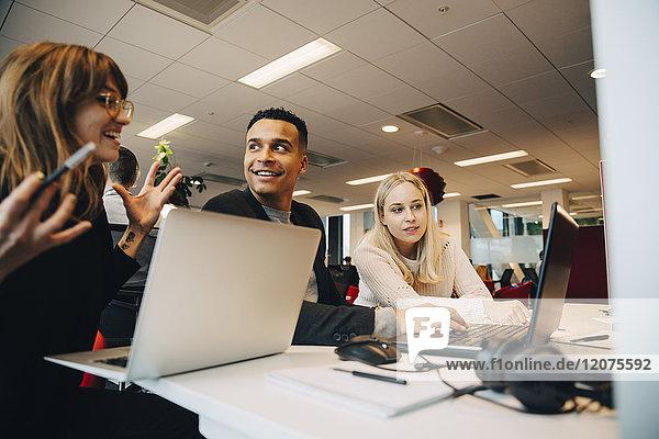 Lächelnde Geschäftsfrau im Gespräch mit Kollegen am Schreibtisch im Büro