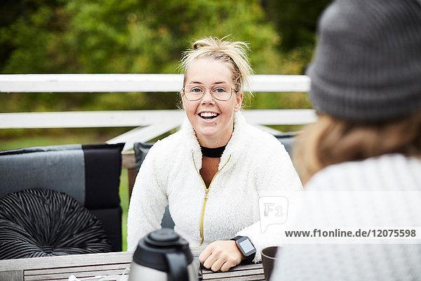 Lächelnde behinderte Frau beim Anblick des männlichen Hausmeisters am Tisch im Hinterhof.