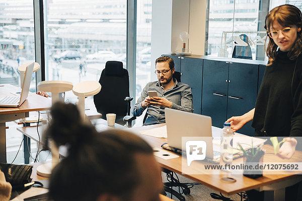 Geschäftsmann sitzt auf einem Stuhl und benutzt dabei ein Smartphone von einer Geschäftsfrau  die im Büro arbeitet.