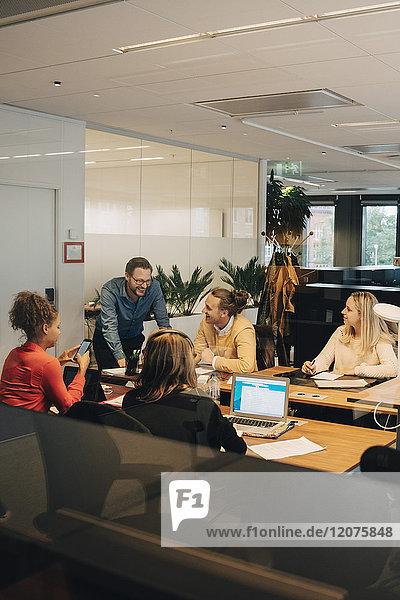 Glückliche multiethnische Mitarbeiter diskutieren im Büro