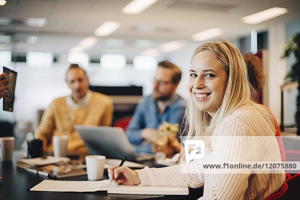 Porträt einer lächelnden jungen Geschäftsfrau mit Kollegen am Konferenztisch im Büro