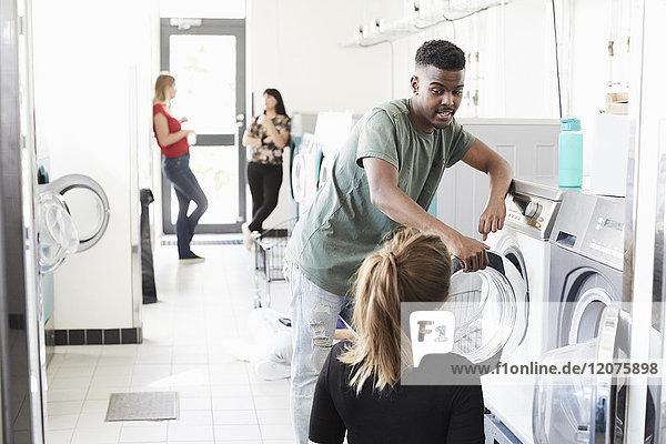 Universitätsstudentin im Gespräch mit der Frau an der Waschmaschine  während Freunde im Hintergrund stehen