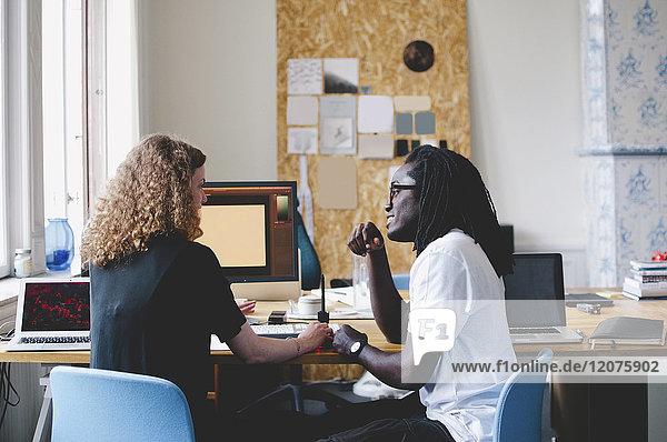 Multiethnische junge Geschäftsleute diskutieren am Tisch im Kreativbüro