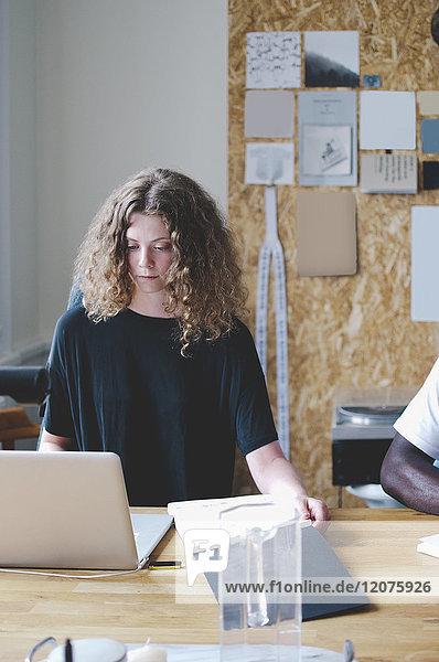 Junge Geschäftsfrau mit Notizblock und Laptop am Tisch im Kreativbüro