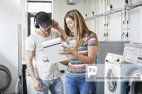 Verwirrte junge Frau  die im Waschsalon eine Waschmittelpackung für einen männlichen Freund zeigt.