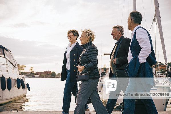 Ältere männliche und weibliche Freunde  die auf dem Pier gegen den Himmel gehen.