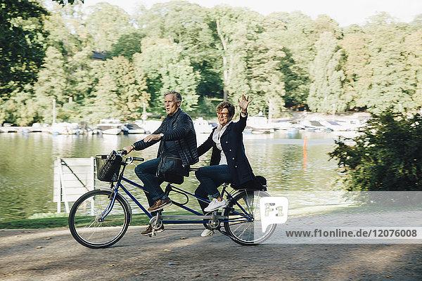 Seniorenpaar genießt Tandem-Radtour am Teich im Park