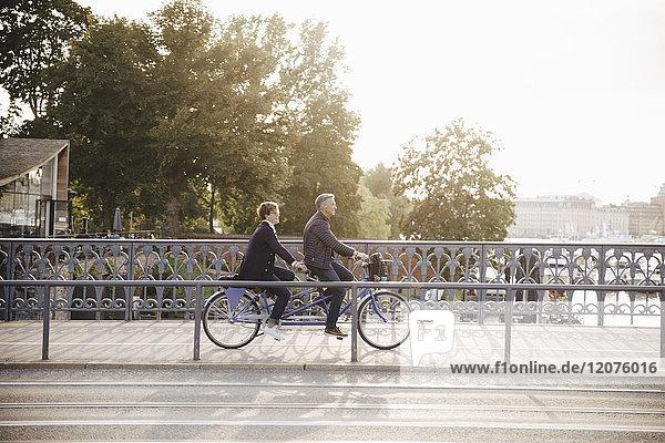 Seitenansicht des Seniorenpaares bei Tandemfahrt auf der Brücke