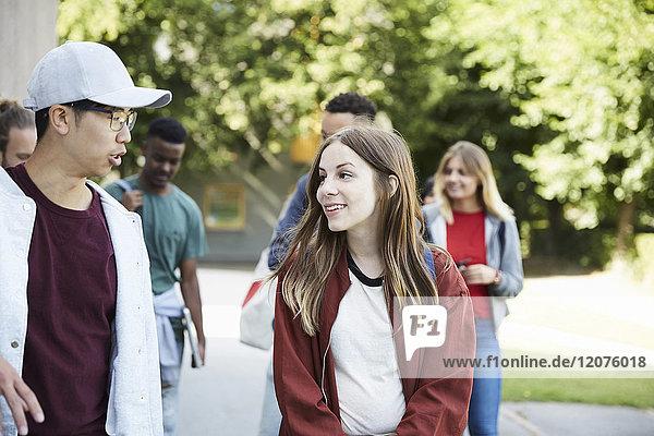 Lächelnde Freunde beim Spaziergang auf dem Uni-Campus an sonnigen Tagen