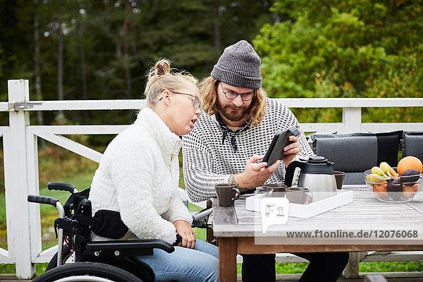 Junge männliche Hausmeisterin mit digitaler Tablette und behinderter Frau im Hof