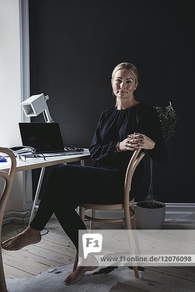 Porträt einer Geschäftsfrau auf dem Stuhl am Schreibtisch im Home Office