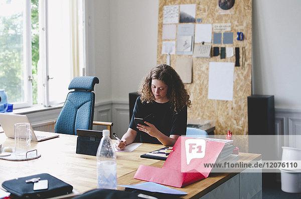 Junge Geschäftsfrau mit Handy beim Schreiben auf Papier am Schreibtisch im Kreativbüro