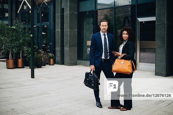 Vollständiges Porträt eines selbstbewussten Geschäftsmannes und einer Geschäftsfrau  die gegen das Bauen in der Stadt stehen