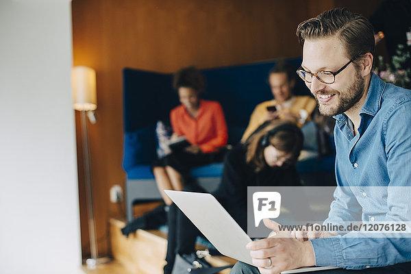 Lächelnder mittelständischer Geschäftsmann mit Laptop im Büro in der Cafeteria