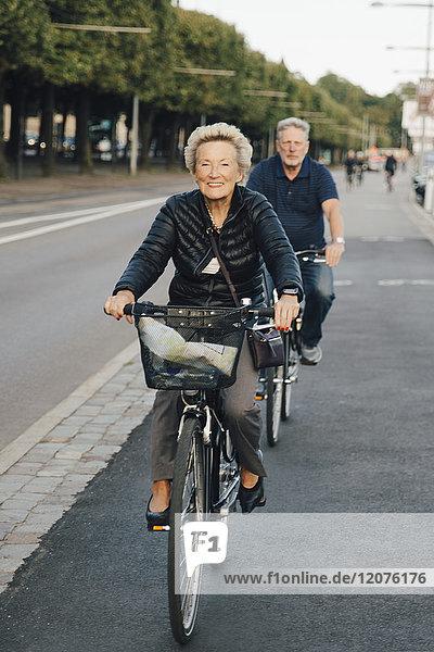 Lächelnde Seniorenfrau mit Mann beim Fahrradfahren auf der Stadtstraße
