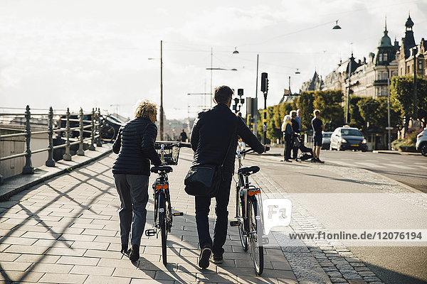 Durchgehende Rückansicht des Seniorenpaares mit Fahrrädern auf dem Bürgersteig in der Stadt