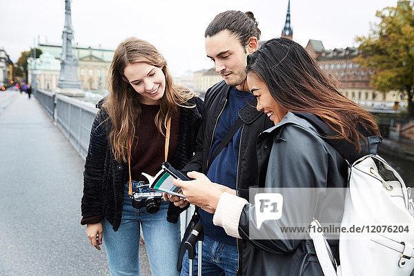 Lächelnde Freunde beim Kartenlesen auf der Brücke in der Stadt