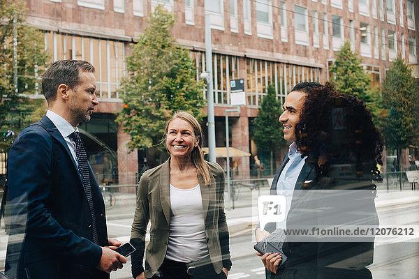 Lächelnde Geschäftskollegen diskutieren im Stehen auf der Straße vom Glas aus gesehen