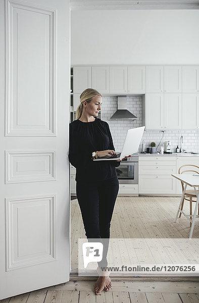 Geschäftsfrau  die den Laptop benutzt  während sie an der Tür im Home Office steht