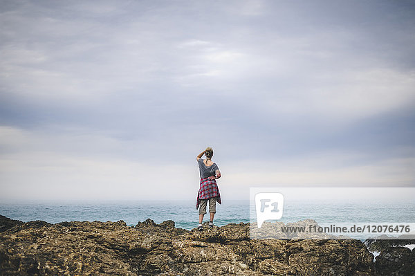 Australia  New South Wales  Woman standing on cliff and looking at view