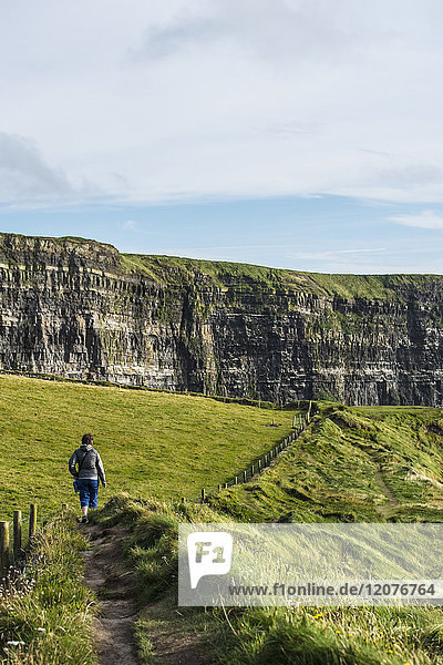 Ireland  Clare County  Woman walking along Cliffs of Moher