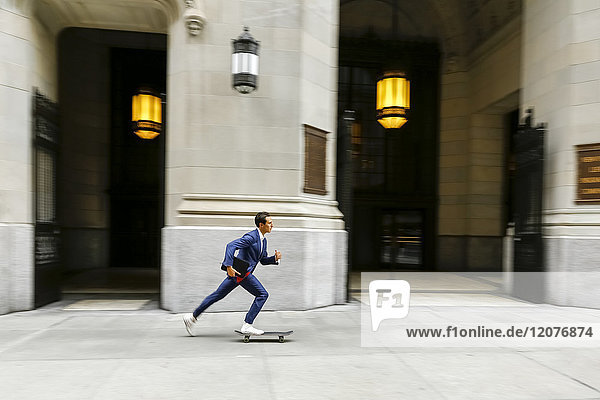 Caucasian businessman skateboarding on urban sidewalk