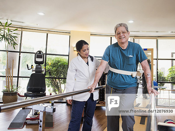 Physical therapist helping walking man