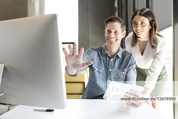 Caucasian man and woman using digital tablet and computer