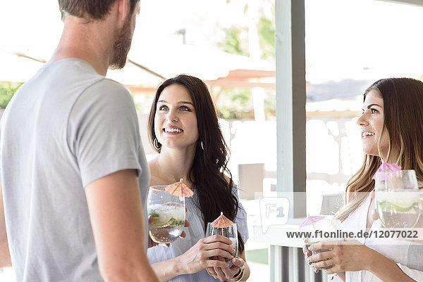 Smiling friends with cold drinks talking outdoors