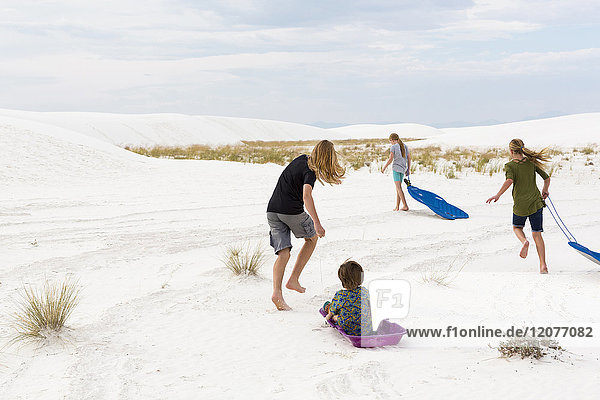 Caucasian boys and girls playing on sleds in sand