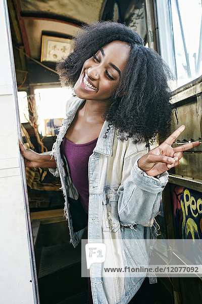 Mixed race woman gesturing peace sign on bus