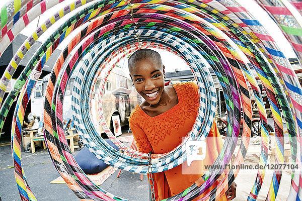 Portrait of smiling bald black woman behind hoops