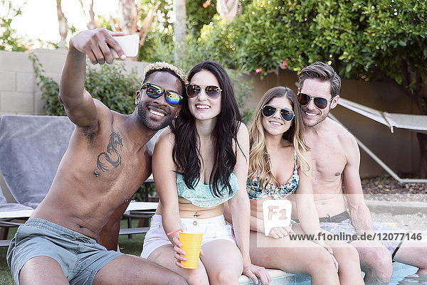 Smiling friends sitting poolside posing for cell phone selfie