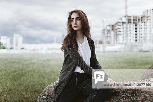 Caucasian woman sitting on rock