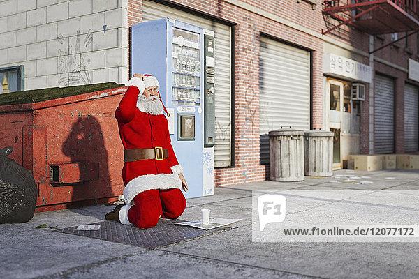 Santa kneeling on sidewalk begging