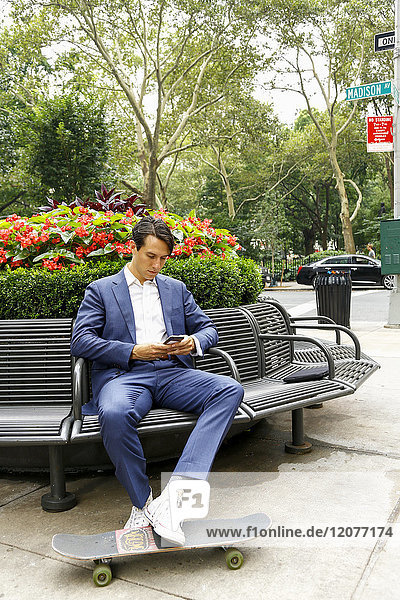 Caucasian businessman on park bench texting on cell phone