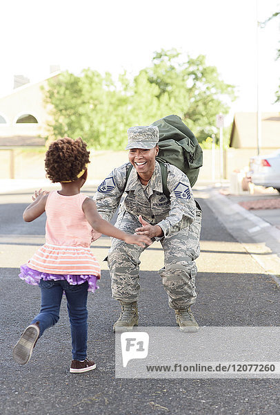 Black woman soldier greeting daughter in street