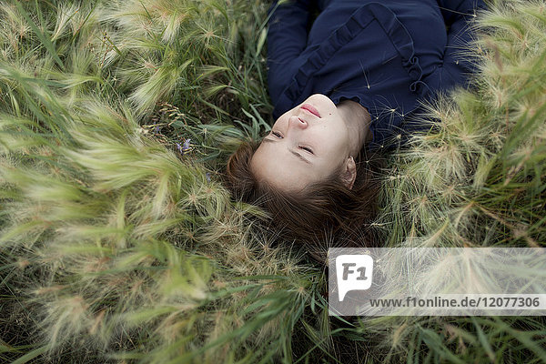 Pensive Caucasian girl laying in field