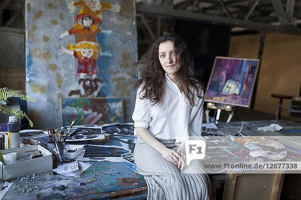 Caucasian artist sitting on table in studio