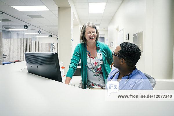 Doctor and nurse laughing near computer