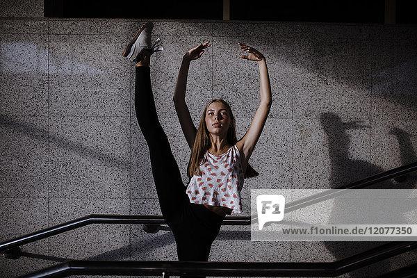 Caucasian woman dancing near staircase railing