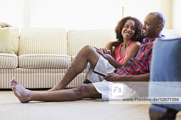 Mixed race couple sitting on floor watching television