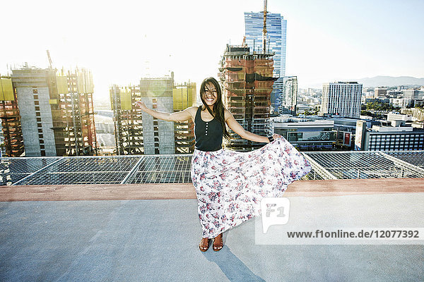 Asian woman dancing on urban rooftop