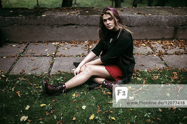Serious Caucasian woman sitting in autumn leaves